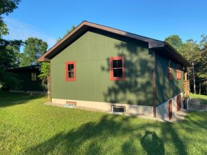side of exterior home painted green with red trim